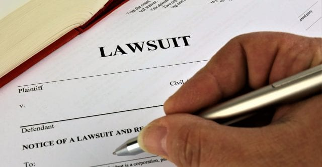 Man With Pen Filling Out Paper That Says Lawsuit